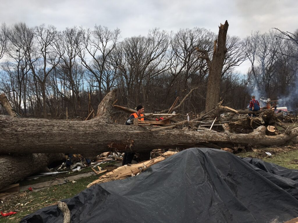 Volunteers cut up fallen trees in East Moline, IL after a deadly Tornado.